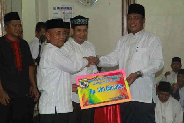 Bupati Pelalawan HM Harris memberikan bantuan diterima lansung oleh Camat Langgam Sugeng Wiharyadi.
